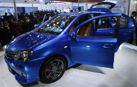 Onlookers stand next to Toyota's compact car 'Etios' at India's Auto Expo in New Delhi January 5, 2010. Toyota said orders for the made-for-India Etios model were easily outpacing its targets so far, providing momentum in the fast-emerging market where the dominance of Maruti Suzuki India remains largely unchallenged. REUTERS/Vijay Mathur/Files