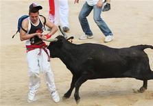 Touro acerta chifrada num participante da festa de Sanfermines, em Pamplona. 12/07/2011 REUTERS/Joseba Etxaburu