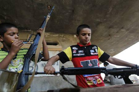 Boys help rebel fighters clean weapons in Misrata, after the rebel fighters returned from the frontline on the outskirts of Zlitan July 12, 2011. REUTERS/Thaier al-Sudani