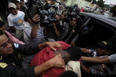 Policiais guatemaltecos escortam Wilfred Stokes (em vermelho), suspeito pelo assassinato do cantor argentino Facundo Cabral. 12/07/2011 REUTERS/Jorge Dan Lopez