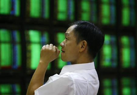 A man looks at monitors displaying stock prices inside a securities company in Taipei October 24, 2008.   REUTERS/Nicky Loh/Files