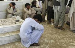 Жители Афганистана у могилы младшего брата президента страны Ахмада Вали Карзая в Кандагаре, 13 июля 2011 года. Два взрыва были слышны в Кандагаре в среду срезу после похорон младшего брата президента Афганистана Ахмада Вали Карзая, сообщили находящиеся в городе журналисты Рейтер. REUTERS/Ahmad Nadeem