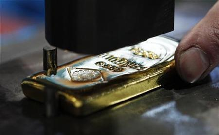 A gold bar is pictured during its stamping at the Austrian Gold and Silver Separating Plant 'Oegussa' in Vienna February 28, 2011. REUTERS/Lisi Niesner