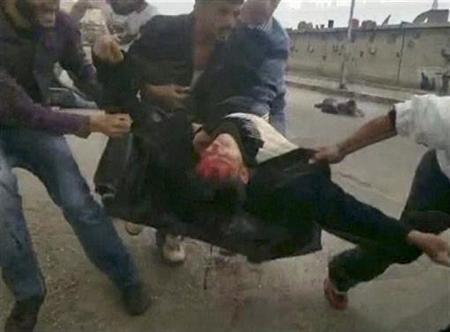 A protester bleeding from the head is carried away during a protest in Damascus in this still image taken from an amateur video footage uploaded to social networking websites on April 23, 2011. REUTERS/Social Media Website via REUTERS TV