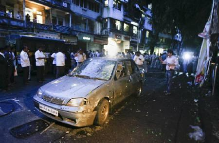 A car is seen damaged at the site of a bomb explosion in the Dadar area of Mumbai July 13, 2011. Three explosions rocked crowded districts of India's financial capital of Mumbai during rush hour on Wednesday, killing at least eight people, media said. REUTERS/Stringer