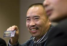 <p>Lai Changxing, one of China's most wanted fugitives, holds his provincial driver's license during a news conference in Vancouver, British Columbia, September 18, 2007. REUTERS/Andy Clark</p>