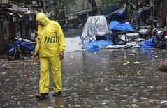 Полицейский осматривает район близ Опера хаус в Мумбаи, 14 июля 2011 года. Три взрыва сотрясли в среду Бомбей, индийский финансовый центр, погибли не менее 17 человек, сообщила пресс-служба индийского правительства. REUTERS/Danish Siddiqui