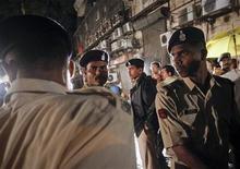 Сотрудники полиции стоят около места взрыва в Бобейе, 13 июля 2011 года.  Полиция Индии приступила к поиску организаторов трех взрывов в Бомбее, в среду унесших жизни по меньшей мере 18 человек. REUTERS/Vivek Prakash