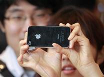 Женщина фотографирует при помощи смартфона iPhone 4 в Сеуле, 10 сентября 2010 года. Подразделение Apple Inc в Южной Корее выплатило компенсацию пользователю смартфона iPhone за несанкционированный сбор данных о его местоположении, сообщили юристы. REUTERS/Jo Yong-Hak