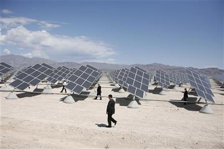 U.S. Secret Service agents walk among the thousands of solar panels generating electricity used at Nellis Air Force Base in Las Vegas, Nevada May 27, 2009 during a visit by President Obama. REUTERS/Jason Reed