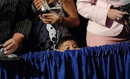 <p>A child strains to see then President George W. Bush at the National Hispanic Prayer Breakfast in Washington June 26, 2008. REUTERS/Jonathan Ernst</p>