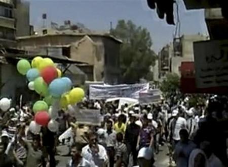 Protesters march during a demonstration against President Bashar al-Assad in the suburb of Qaboun, Damascus in this still image taken from video uploaded on a social media website on July 15, 2011. Syrian forces killed at least 32 civilians on Friday, including 23 in the capital Damascus, in an intensifying crackdown on protests against President Bashar al-Assad, activists said. REUTERS/Social Media Website via REUTERS TV