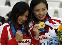 A chinesa Wu Minxia (D) e He Zi posam com suas medalhas de ouro durante a cerimônia de entrega de medalhas do 14o Campeonato Mundial de Natação, em Xangai. Wu Minxia conquistou seu quinto título mundial de salto no trampolim sincronizado de três metros. 16/07/2011 REUTERS/Bobby Yip