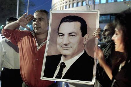 A supporter of former president Hosni Mubarak kisses a poster of Mubarak in downtown Cairo in this April 17, 2011 file photo. Mubarak, who was ousted in February and who has been detained in a hospital in the Red Sea resort of Sharm el-Sheikh, has fallen into a coma, his lawyer said on Sunday. REUTERS/Asmaa Waguih/Files