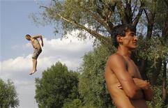 Мужчина прыгает в реку в Мытищах (Подмосковье), 3 июля 2011 года. Жаркая рабочая неделя с почти ежедневными осадками ждет жителей Москвы, предсказывают синоптики. REUTERS/Denis Sinyakov