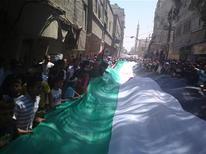 Демонстранты держат огромный флаг во время акции протеста в Дамаске, 17 июля 2011 года. Сирийские правительственные войска окружили в воскресенье город на границе с Ираком, население которого вышло на улицы вместе с выступившими против режима президента Башара аль-Асада военными, сообщили местные жители. REUTERS/Handout