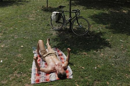 A man suns himself in McCarren Park on a hot summer day in New York July 12, 2011. REUTERS/Lucas Jackson