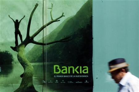 A man walks past a poster of savings bank Bankia in Madrid June 28, 2011. REUTERS/Susana Vera