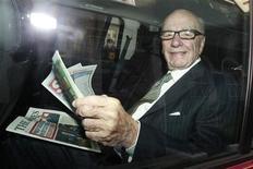 Глава News Corporation Руперт Мёрдок держит газету The Sun, сидя в машине в Лондоне, 11 июля 2011 года. Группа хакеров взломала сайт самого продаваемого в Британии таблоида Руперта Мёрдока Sun, сообщив на первой полосе о смерти находящегося в центре международного скандала медиамагната. REUTERS/Luke MacGregor