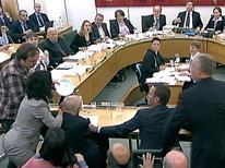 Homen atinge o presidente-executivo da News Corp, Rupert Murdoch, com um prato cheio de espuma branca durante audiência no parlamento britânico. 19/07/2011 REUTERS/Parbul TV via Reuters Tv