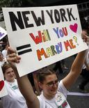 <p>A girl holds a sign reading, 'New York, Will You Marry Me?' as she takes part in the Gay Pride Parade in New York June 26, 2011. REUTERS/Jessica Rinaldi</p>