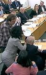 Homem tenta acertar uma torta de espuma branca no chefe-executivo da News Corp, Rupert Murdoch, durante audiência no Parlamento britânico. 19/07/2011  REUTERS/Parbul TV via Reuters Tv