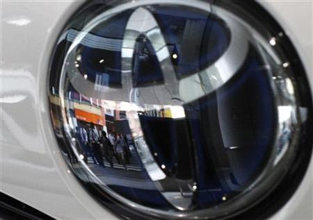 People are reflected on a Toyota Motor vehicle logo at the company showroom in Tokyo June 10, 2011.REUTERS/Toru Hanai