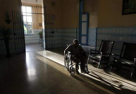 An elderly man rolls along in his wheelchair at the Santovenia Asylum in Havana July 6, 2009. REUTERS/Enrique De La Osa