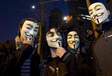 """Сторонники WikiLeaks в масках хакерской группы """"Anonymous"""" на демонстрации в Мадриде, 11 декабря 2010 года. ФБР арестовало по меньшей мере 14 человек во вторник в рамках крупномасштабной операции по поиску хакерской группы Anonymous, сообщил источник в правоохранительных органах. REUTERS/Paul Hanna"""