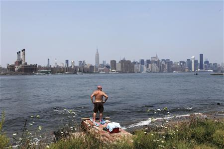 A man suns himself during a hot summer day at a park in the Brooklyn borough of New York July 20, 2011. REUTERS/Lucas Jackson