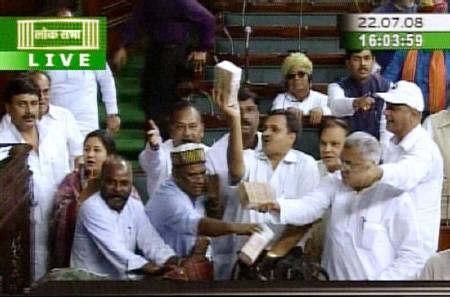 A video grab shows India's opposition lawmakers displaying wads of cash they said were offered as bribes to abstain from voting during a two-day debate inside the parliament in New Delhi July 22, 2008. REUTERS/ANI/Files