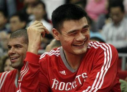 Yao Ming (R) of the Houston Rockets laughs as he sits with his teammate Shane Battier on the bench during the NBA China Games series basketball game at the Guangzhou International Sports Arena in Guangzhou, Guangdong province October 16, 2010. REUTERS/Joe Tan