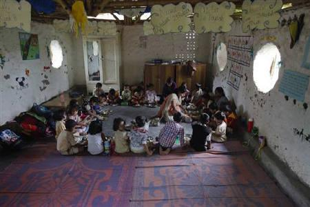Students eat their lunch inside a classroom constructed from mud and old cement bags at the Aman Setu school in Pune, about 190km (118 miles) from Mumbai, July 20, 2011. REUTERS/Vivek Prakash