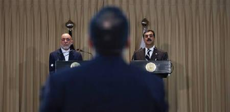 A journalist stands to ask a question during a news conference with Pakistan's Prime Minister Yusuf Raza Gilani (R) and Afghan President Hamid Karzai at the prime minister's residence in Islamabad June 11, 2011. REUTERS/Faisal Mahmood/Files