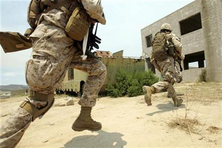 U.S. Marines conduct a search for insurgents during a training simulation of a search through an Iraqi city built at the U.S. Marine Base in Camp Pendleton, California, June 29, 2006. In this exercise 170 mostly reserve soldiers secured ''Combat Town'' in about one hour. REUTERS/Mike Blake