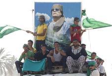 Сторонники Муаммара Каддафи на фоне портрета ливийского лидера в пригороде Триполи, 15 июля 2011 года. Ливийский лидер Муаммар Каддафи отклонил в четверг возможность сотрудничества с противостоящими его режиму мятежниками, поставив под вопрос усилия Запада добиться окончания пятимесячного кровопролитного конфликта за столом переговоров. REUTERS/Louafi Larbi
