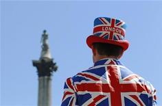 Уличный артист, одетый в цвета британского флага, смотрит на памятник адмиралу Нельсону на Трафальгарской площади Лондона. Фотография сделана 26 июня 2011 года REUTERS/Luke MacGregor