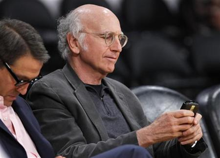 Actor and comedian Larry David checks his phone as he sits courtside watching the Los Angeles Lakers play the Dallas Mavericks during Game 2 of the NBA Western Conference semifinal basketball playoff in Los Angeles, California May 4, 2011. REUTERS/Lucy Nicholson