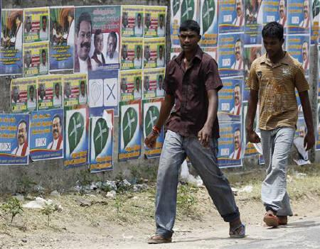 Two boys walk past local government election campaign posters in Jaffna, about 304 km (189 miles) north of Colombo, July 22, 2011. REUTERS/Dinuka Liyanawatte