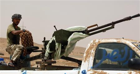 A rebel fighter with weapons stands in a vehicle outside the Bir-Ayyad gate near the city of Zintan in the western mountains, 120 km (75 miles) southwest of the capital Tripoli, July 23, 2011. REUTERS/Zoubeir Souissi