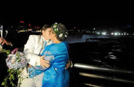 Cheryle Rudd (L) and Kitty Lambert kiss after being married at the stroke of midnight, at the brink of Niagara Falls, in Niagara Falls, New York, by the city's mayor, Paul Dyster, July 24, 2011.REUTERS/Doug Benz