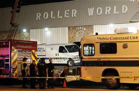 Police officers stand outside of the Roller World Forum were five people were murdered in Grand Prairie, Texas July 23, 2011. REUTERS/Mike Stone