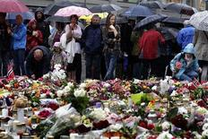 People pay their respect beside floral tributes outside the Oslo Cathedral July 24, 2011.  REUTERS/Cathal McNaughton