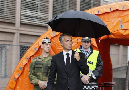 Norwegian Prime Minister Jens Stoltenberg holds an umbrella as he walks in front of the government building in Oslo July 24, 2011. REUTERS/Wolfgang Rattay