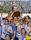 Diego Lugano (centro) segura o troféu da Copa América com seus colegas de equipe após a derrota contra o Paraguai na final em Buenos Aires.  O Uruguai conquistou o título no domingo ao derrotar o Paraguai por 3 x 0. 24/07/2011  REUTERS/Martin Acosta