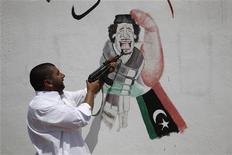 Повстанец целится в изображение Муаммара Каддафи на стене в Зинтане, 15 июля 2011 года. Муаммар Каддафи и члены его семьи смогут остаться на территории Ливии, если он отречется от власти, цитирует высокопоставленного лидера повстанцев Мустафу Абдель Джалиля газета Wall Street Journal.  REUTERS/Ammar Awad
