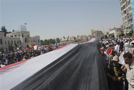 People hold a giant Syrian flag during a protest against President Bashar al-Assad after Friday prayers in Hama July 22, 2011. REUTERS/Handout