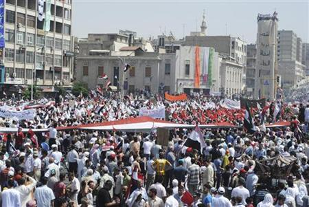People holding a giant Syrian flag protest against President Bashar al-Assad after Friday prayers in the city center of Hama July 22, 2011. REUTERS/Handout