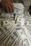 Кассир складывает деньги в банке в Сеуле, 4 мая 2010 года. Доллар опустился до трехмесячного минимума к корзине валют в среду, так как рынки напуганы перспективами дефолта и понижения долгового рейтинга США, кроме того инвесторы ждут, проведет ли Япония интервенцию, чтобы ослабить иену. REUTERS/Truth Leem