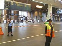 Сотрудники служб безопасности проверяют центральный вокзал Осло, 27 июля 2011 года. Центральный вокзал Осло был эвакуирован, а отправления всех поездов и автобусов - задержаны из-за найденного в здании подозрительного чемодана, сообщил представитель железнодорожной компании NSB. REUTERS/Ole-Tommy Pedersen/Scanpix
